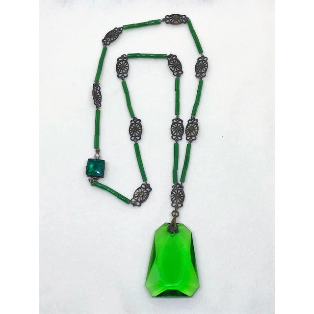 Circa 1920s necklace of green glass tube beads interspaced with ornate brass links hung with a green faceted glass...