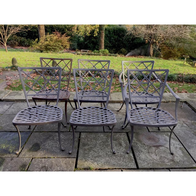 A chic outdoor metal and glass oval dining table and set of lattice back grey metal chairs, two armchairs and 4 side,...
