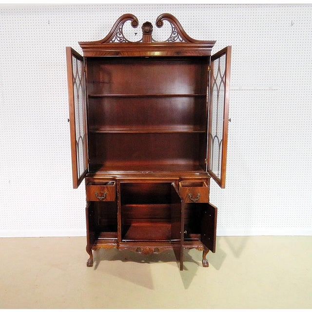 Georgian style flamed mahogany china cabinet with ball & claw feet. 2 doors containing 2 shelves over 2 drawers and 3...