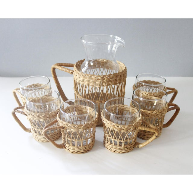 Lovely vintage glass serving pitcher with 6 matching cups. Each has a removable wicker caddy with a handle. Excellent...