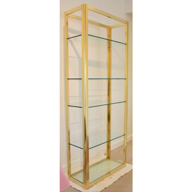 Milo Baughman-style gold wash etagere with thick glass shelves. A beautiful, nearly mint condition shelving unit in a...