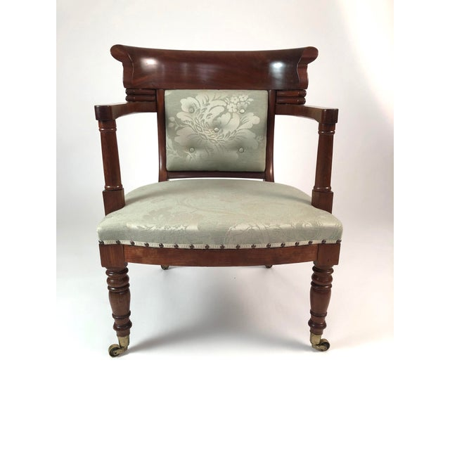 A generously proportioned and comfortable 19th century French Empire period fauteuil in mahogany, the curved tablet back...