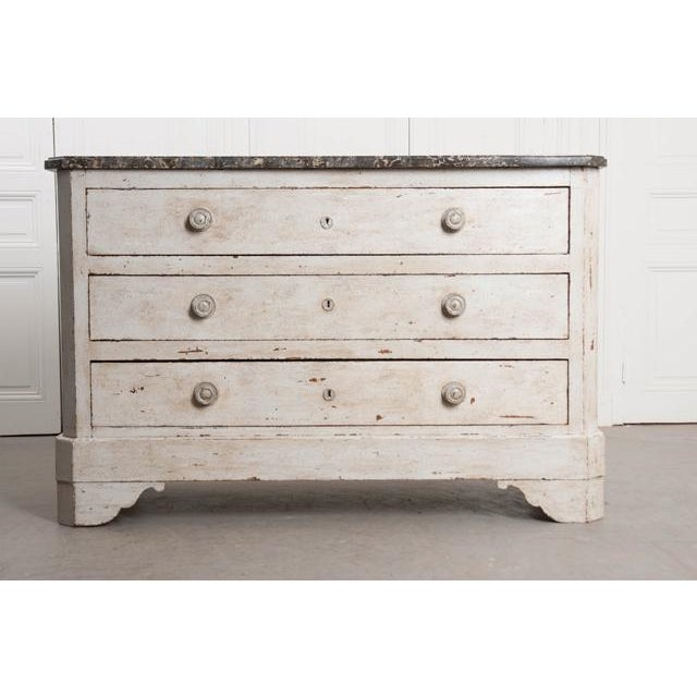 An attractive commode, painted and topped in marble, from 19th century France. The three-drawer case piece is wide and...