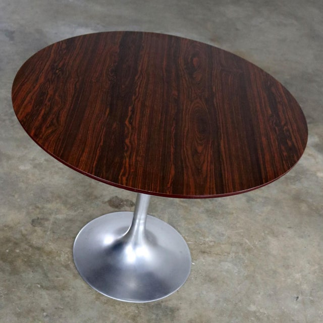 Classic mid-century modern Saarinen style tulip table with polished aluminum base and round woodgrain laminate top....