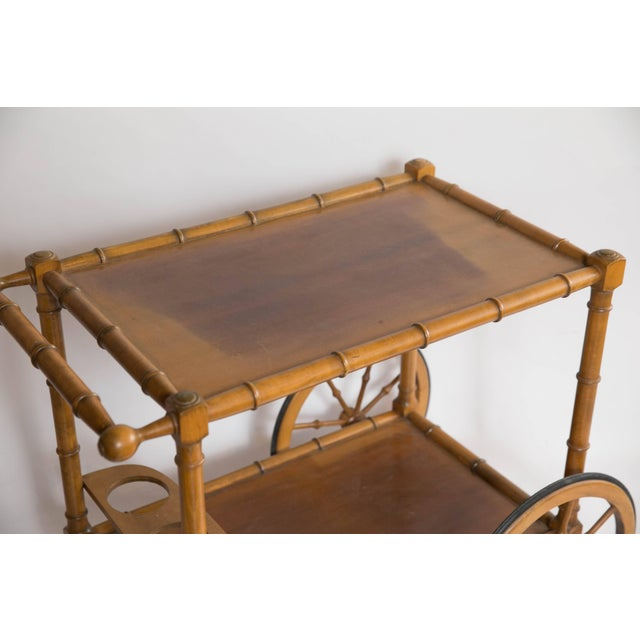 Get the party rolling with this 1950s faux bamboo bar cart from France. With two wooden tiers and a holder for three...