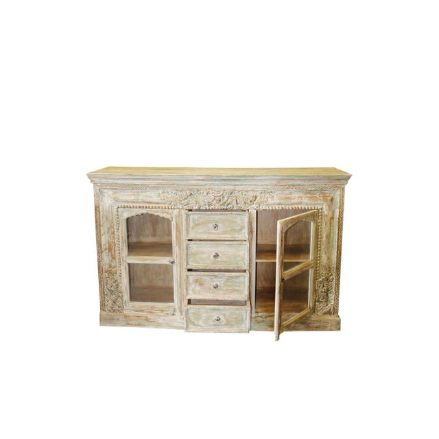 The vintage ornately carved ivory with hints of green Solid Wooden sideboard comes from India and has brass cladded floral...