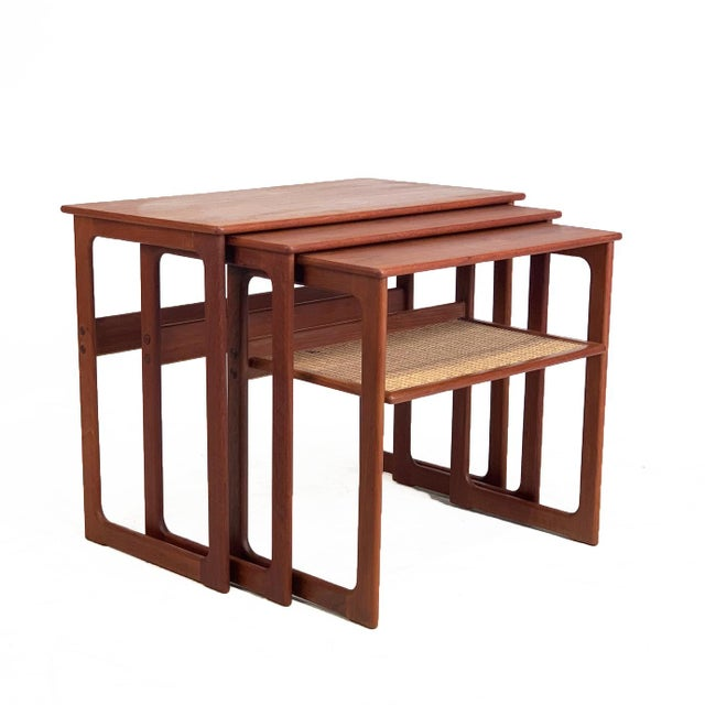 A sleek set of three teak nesting tables with the smallest table having a caned lower shelf. Resting on solid teak legs...