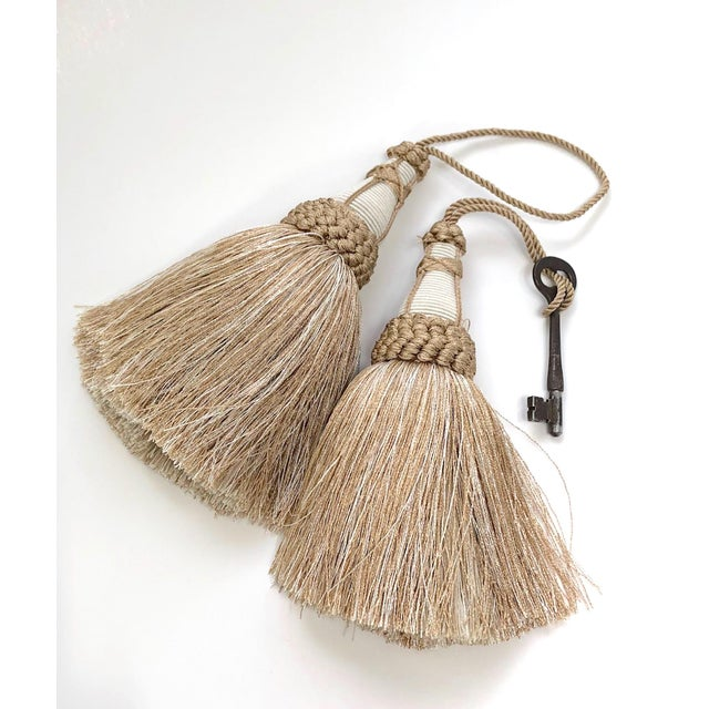 Pair of handmade gold and white colored key tassels with looped ruche, knit detailing, twisted cord and full skirt. Please...