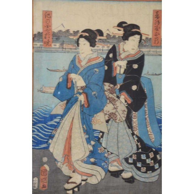 Lovely blue early Japanese Woodblock print depicting two Geisha by the water wearing elaborate Kimonos. Signed with stamp...