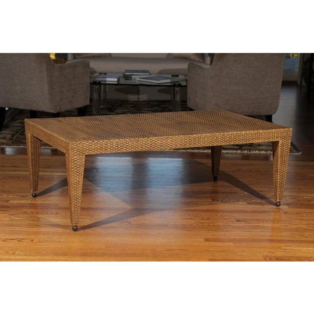 An exceptional vintage coffee table, circa 1985. Stout, expertly crafted hardwood form veneered in basketweave raffia-aged...