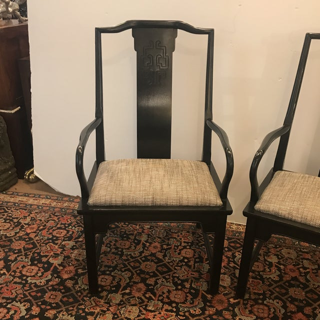 A pair of classically styled Asian style ebonized wood armchairs. The nubby textured woven padded seats contrast nicely to...
