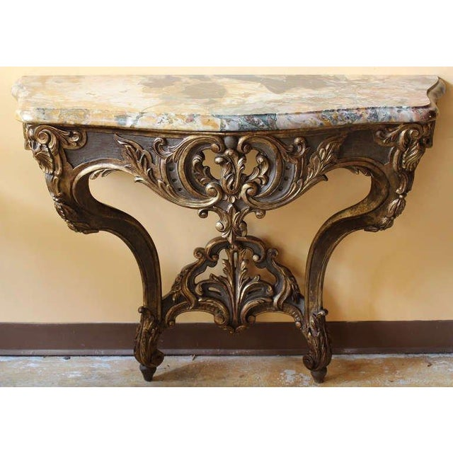 Beautifully carved, gilded and painted wood console table with a gorgeous marble top. It shows curved lined and sinuous...