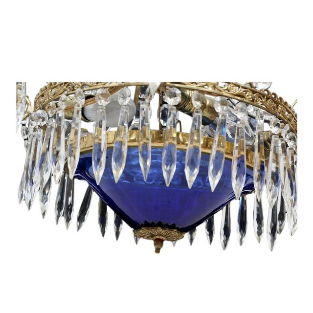 Antique crystal Swedish chandelier with a tinted blue glass bowl. Octagon and tear shaped crystals with a brass ornametal...