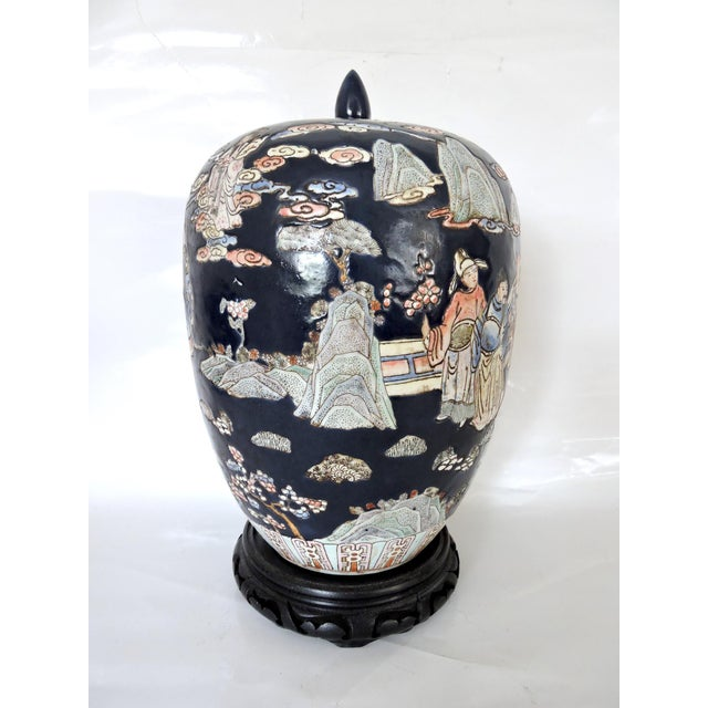A very detailed hand painted old Chinese ginger jar with a continuous theme on a navy blue background. Family scenes,...
