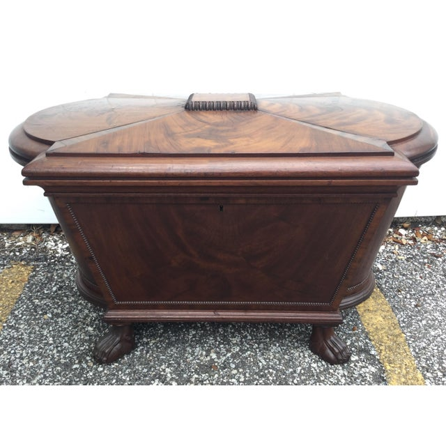 A large regency carved mahogany sarcophagus form dome top cellarette, with four paw feet, a hinged stepped lid. Exquisite...
