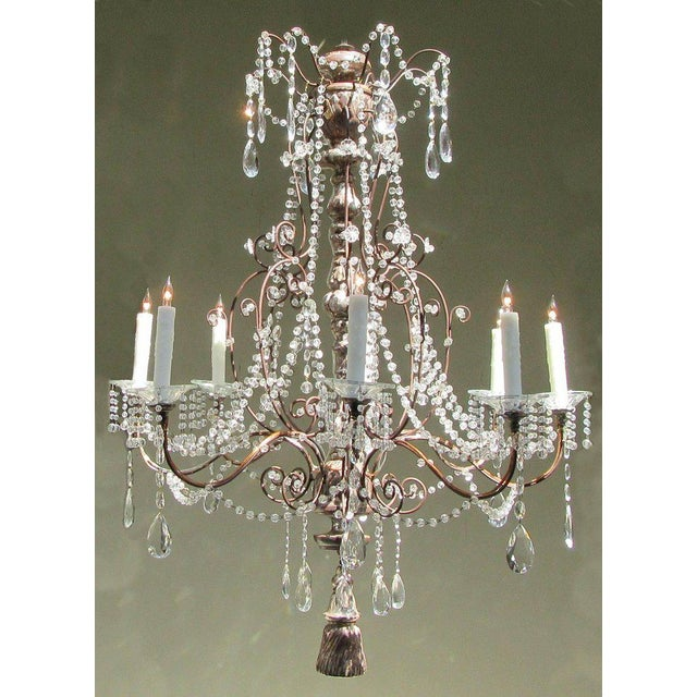 A large early 19th century Italian Baroque crystal chandelier, circa 1810, with silvered carved wood stem, eight tole...