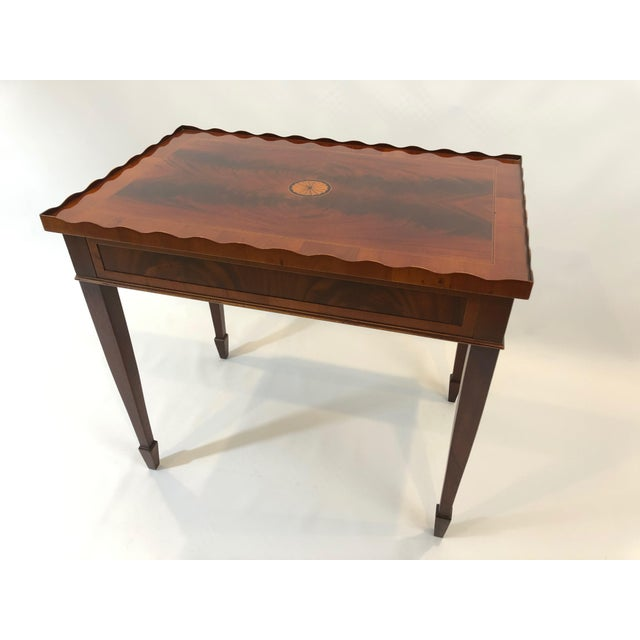 An elegant flame mahogany tea table by Heckman having a pretty scalloped pie crust edge, satinwood & ebony fan inlay, and...