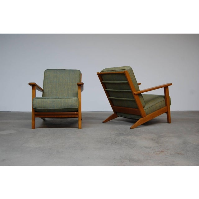 Pair of low lounge chairs in oak from France, circa 1950. Chairs have loose cushions and have been reupholstered in raw...