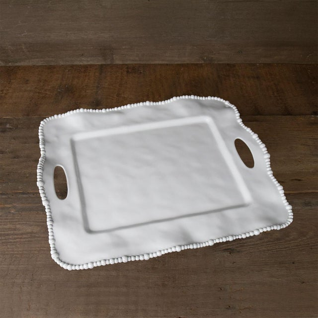 This tray is an OPRAH'S PICK! An ample serving area and notched handles make this sparkling White Rectangular Tray with...