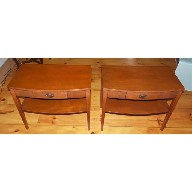 Vintage pair of Hepplewhite style accent tables have convex front edge above single dovetailed drawer with brass pulls and...