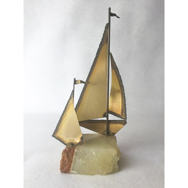A 1970s Mario Jason Originals Brass Sailboat on Onyx. This brass sailboat has a distinct touch of 70's retro flair! The...