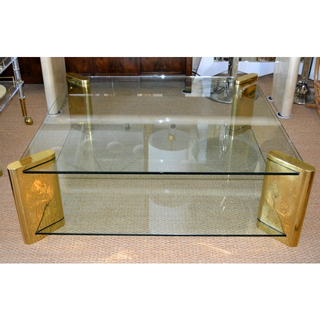 Monumental lovely Mid-Century Modern low Brass and Glass coffee table by Karl Springer. Four corner elements constructed...