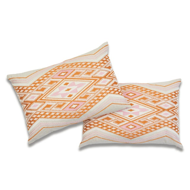 """This 16"""" x 24"""" pillow features Bayeta Embroidery in Pink & Orange. Inflected with a chic tribal aesthetic, this..."""