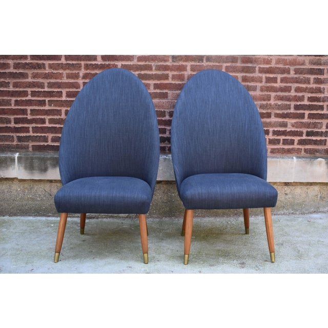A pair of high back occasional slipper chairs in the style of Nanna Ditzel. The chair is accented with an upholstered...