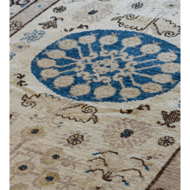 This antique Khotan rug has an ivory field with a vase at each end issuing an angular floral arrangement flanked by...