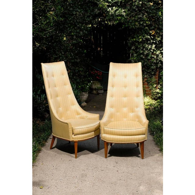 American pair of Mid-Century Modern high back tufted slipper chairs with a loose cushion and resting on a wooden base with...