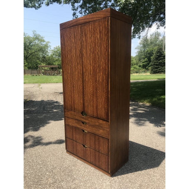 Large wardrobe or armoire by baker furniture. Walnut veneer. Scalloped door corners for pulls. Gold gilted background...