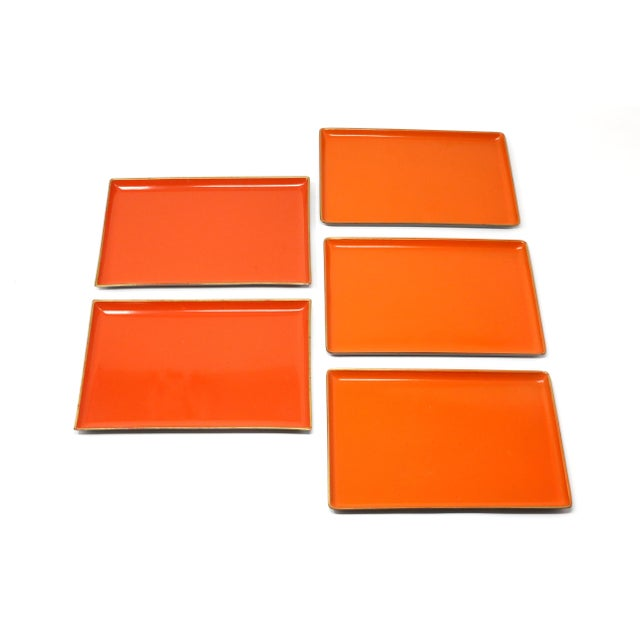 A set of five orange lacquerware melamine airplane/tip trays. Three trays (labeled Asahi/made in Japan) are slightly...