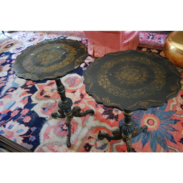 Pair of chinoiserie Swedish tilt-top tables with scalloped top resting on a turned tripod pedestal base. Gold leaf...