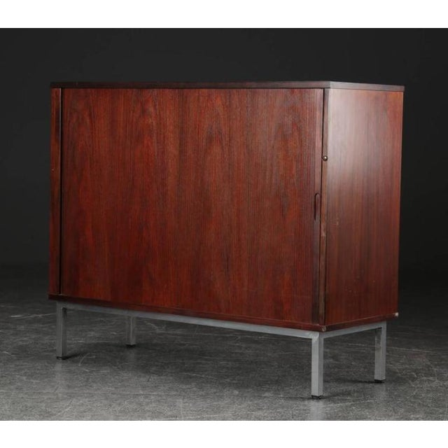 - Cabinet veneered in rosewood with louvered doors - Mounted with steel legs - Made in Denmark in the 1960s