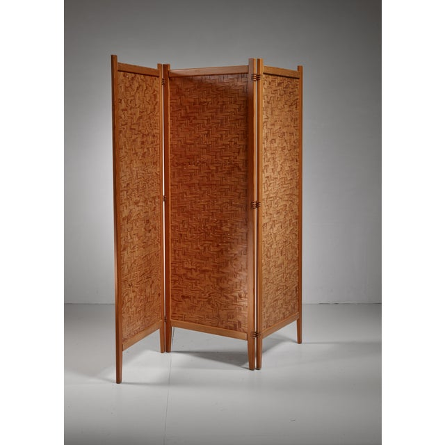 A Swedish folding screen or room divider by Alberts, Tibro. The three part screen is made of a pine frame with thin, woven...
