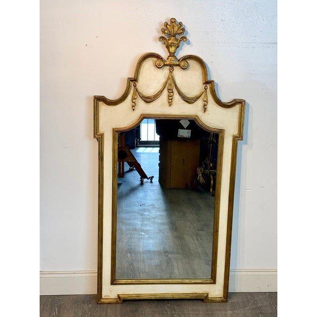 Italian neoclassic giltwood and parcel gilt mirror, of cartouche form with removable floral urn finial. The lower tier...
