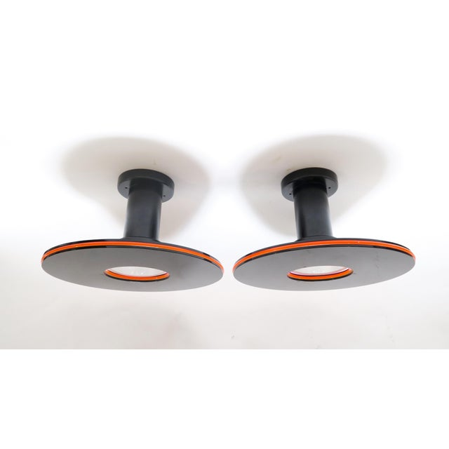 Pair of unique vintage Fredrick Ramond round ceiling fixtures. Black acrylic and metal, with bright orange edge detail....