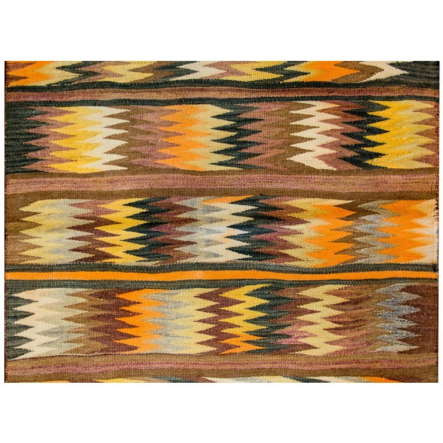 A wonderful early 20th century Persian Baluchi kilim rug with a bold multi-colored zigzag pattern arranged in stripes with...