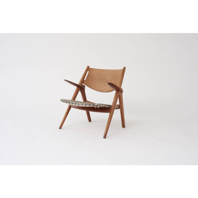 A super early and original example of the classic Hans Wegner CH-28 sawbuck armchair. Oak frame, with lovely grain, and...