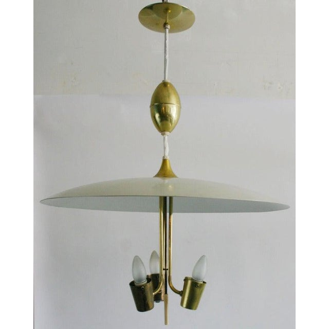 White enameled metal and brass hanging pendant attributed to Gerald Thurston for Lightolier. Extendable cable allows 24 to...