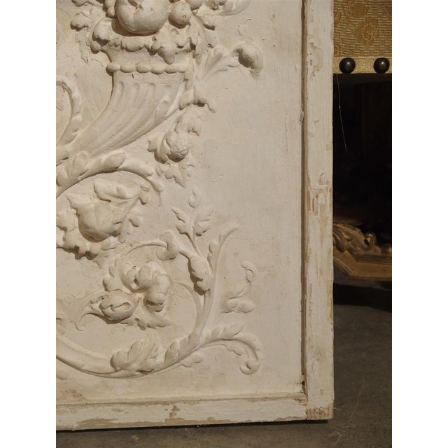 From France, this framed plaster bas relief panel depicts two cornucopias with scrolling rinceau at the center and sides....