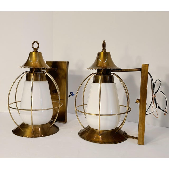 A unique pair of vintage brass cage nautical lights with milk glass lens. These lights will give you that unique vintage...