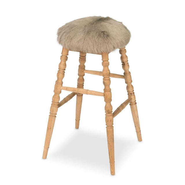 Estimated Retail Price: $744. The 'Winoma' bar stool is made from wood and is upholstered in a beige goatskin rug....
