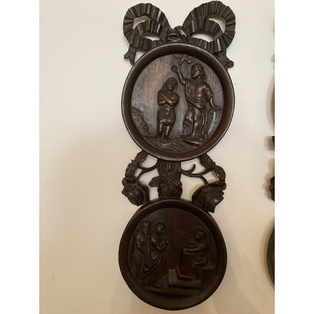 A pair of wooden carved religious plaques. French ribbon carving detail. Wear appropriate for age.