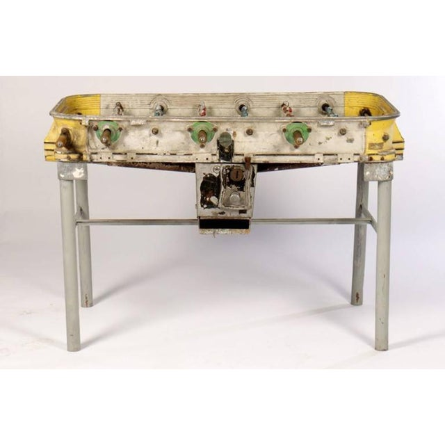 A yellow vintage cast aluminum foosball table circa 1940.