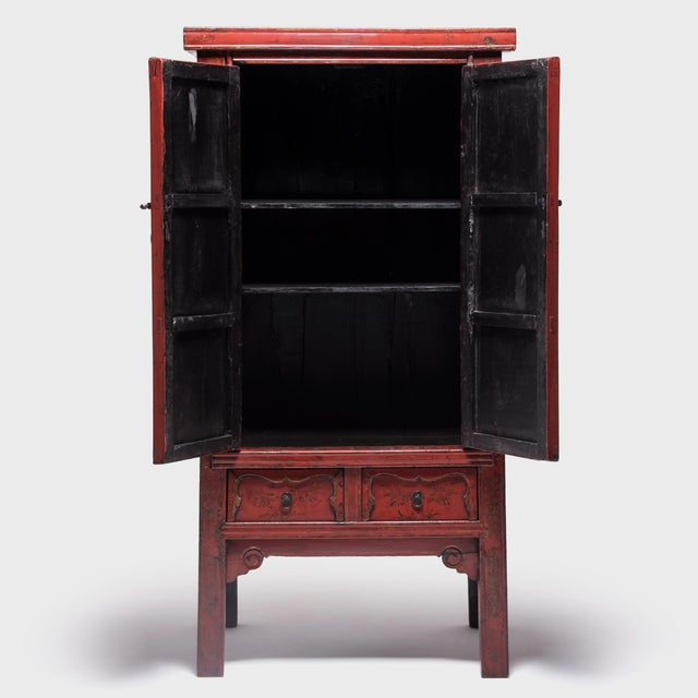 The lyrical lines and brilliant red lacquer of this stately 19th-century cabinet must have proved irresistible to the...
