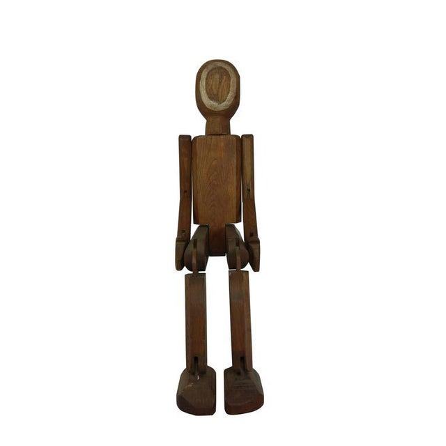 This is a one of a kind hand-carved articulating man from France, circa 1940. The painted white circles on his head...