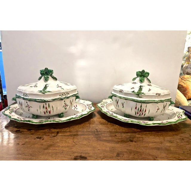 This is a superb pair of early 19th c. French Faience Tureens with Under Plates. The rich green and scarlet tones of the...