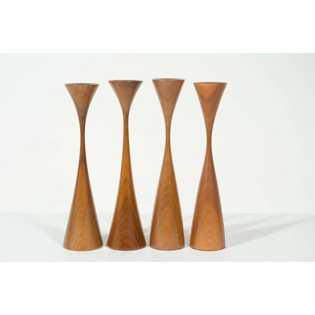 A sculptural set of four candlesticks hand turned in walnut; each in an elongated hourglass form, one slightly shorter...