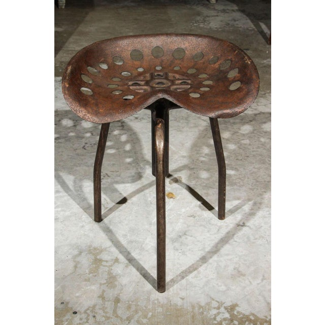 Set of four mid-century industrial swivel chairs on tripod legs from Belgium.